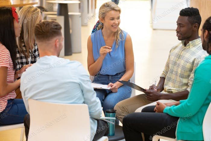 Diverse business people sitting together and having a group discussion