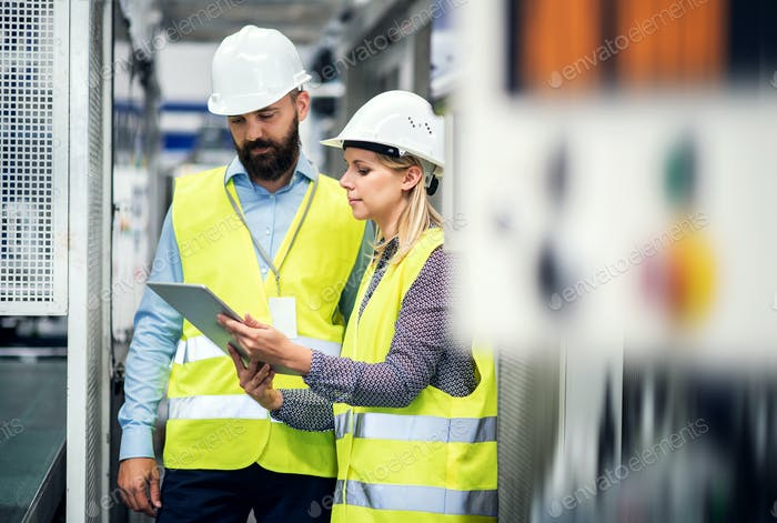 A portrait of an industrial man and woman engineer with tablet in a factory, talking.