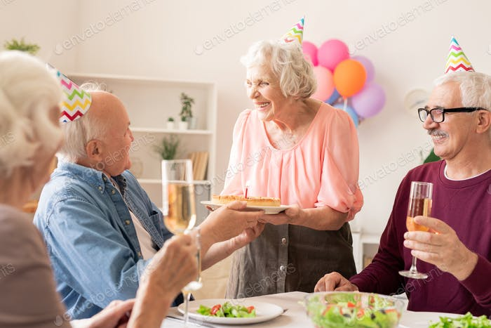 Cheerful aged female with birthday cake looking at one of friends