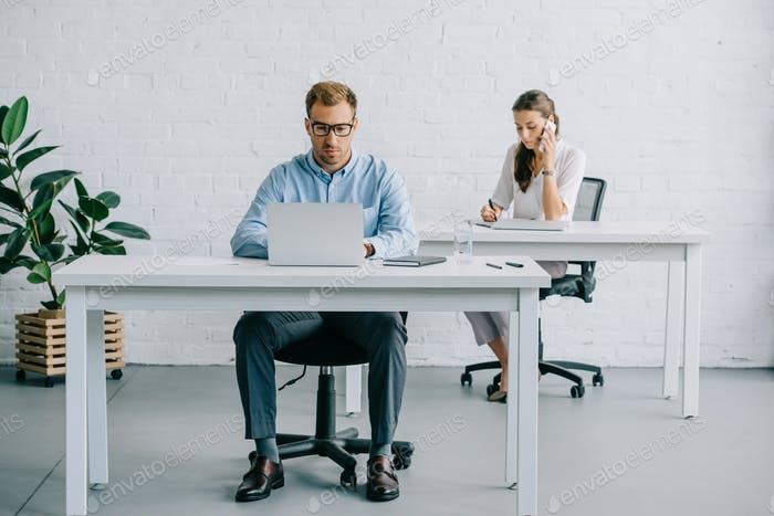young business people using digital devices while working in office