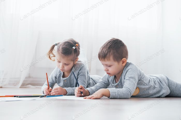 Children lie on the floor in pajamas and draw with pencils. Cute child painting by pencils