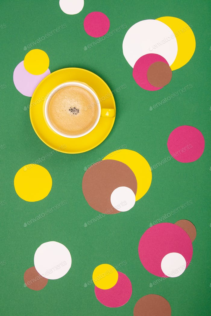 Cup of Coffee and colorful paper circles on green paper backgrou