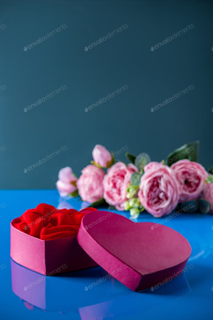 Heart shaped open gift box on blue background.