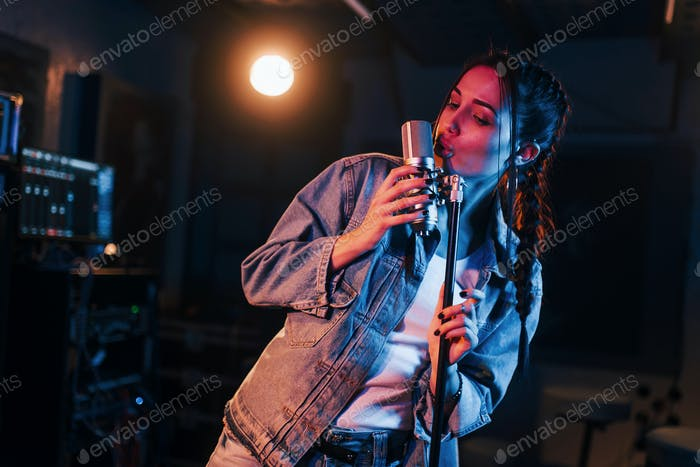 Young beautiful female singer rehearsing in a recording studio