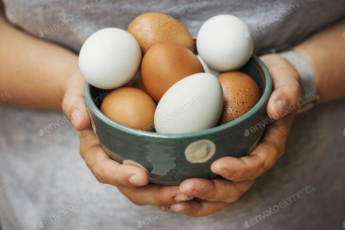 Eine Frau hält Schüssel mit frischen braunen und weißen Eiern.