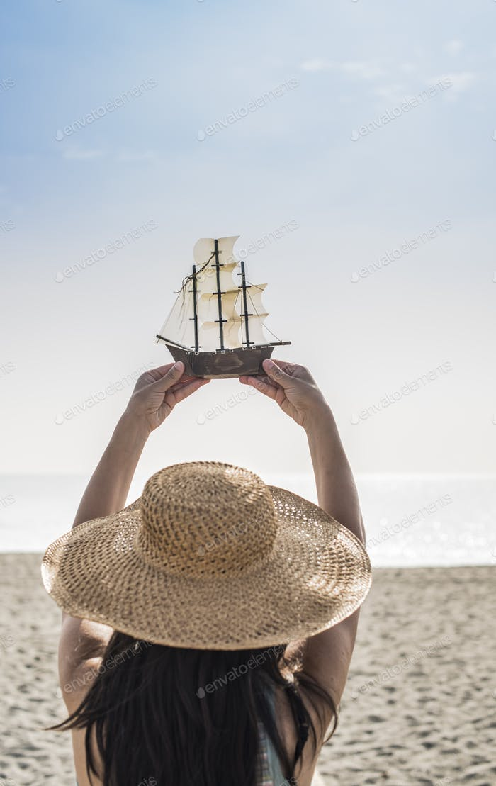 Woman hold boat model on the beach
