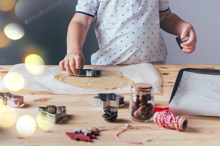 Kleiner Junge bereitet Weihnachtskekse vor. Rohteig, Ausstecher, Urlaubsdekoration auf einem Holztisch.