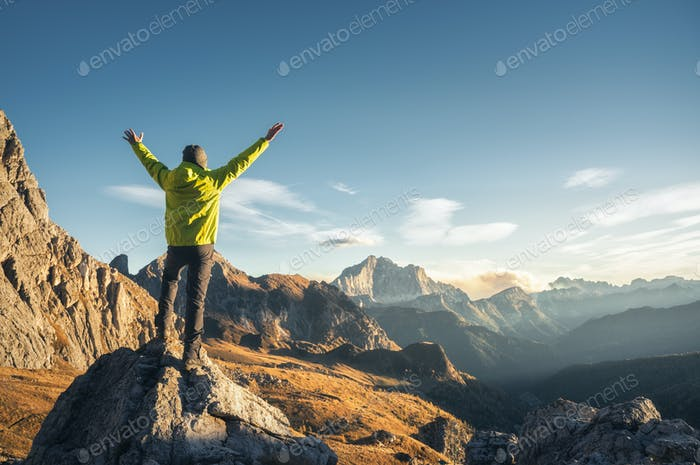Man on the stone with raised up arms against mountain valley
