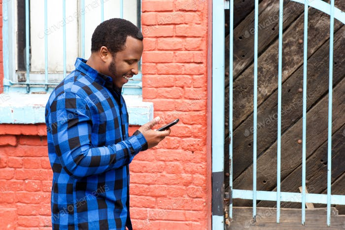 young black man walking in city with mobile phone