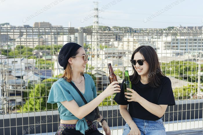 Two young Japanese women sitting on a rooftop in an urban setting, drinking beer.