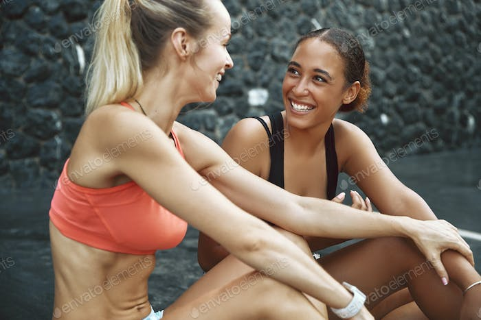 Two laughing young women sitting together outside after jogging