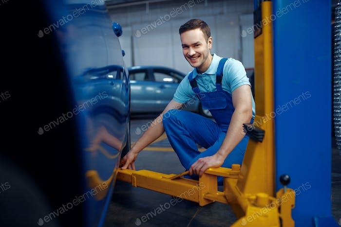 Worker in uniform fix vehicle on lift, car service