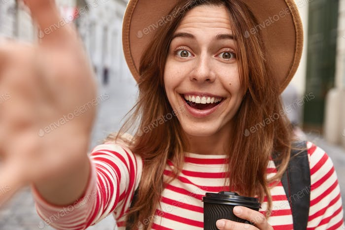 Close up shot of happy female traveler has hands outstretched at camera, makes selfie portrait, drin