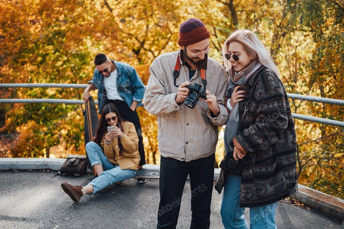 Company of friends relaxing and photographing in autumn park