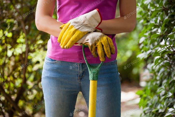 Mittenteil der Frau mit Gartengabel stehend inmitten von Pflanzen