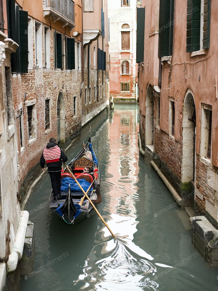 A gondola boat gliding down a small narrow waterway, between historic houses in the city of Venice.