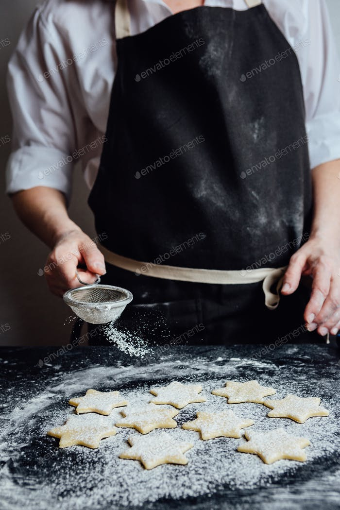 Person putting raw cookies to flour