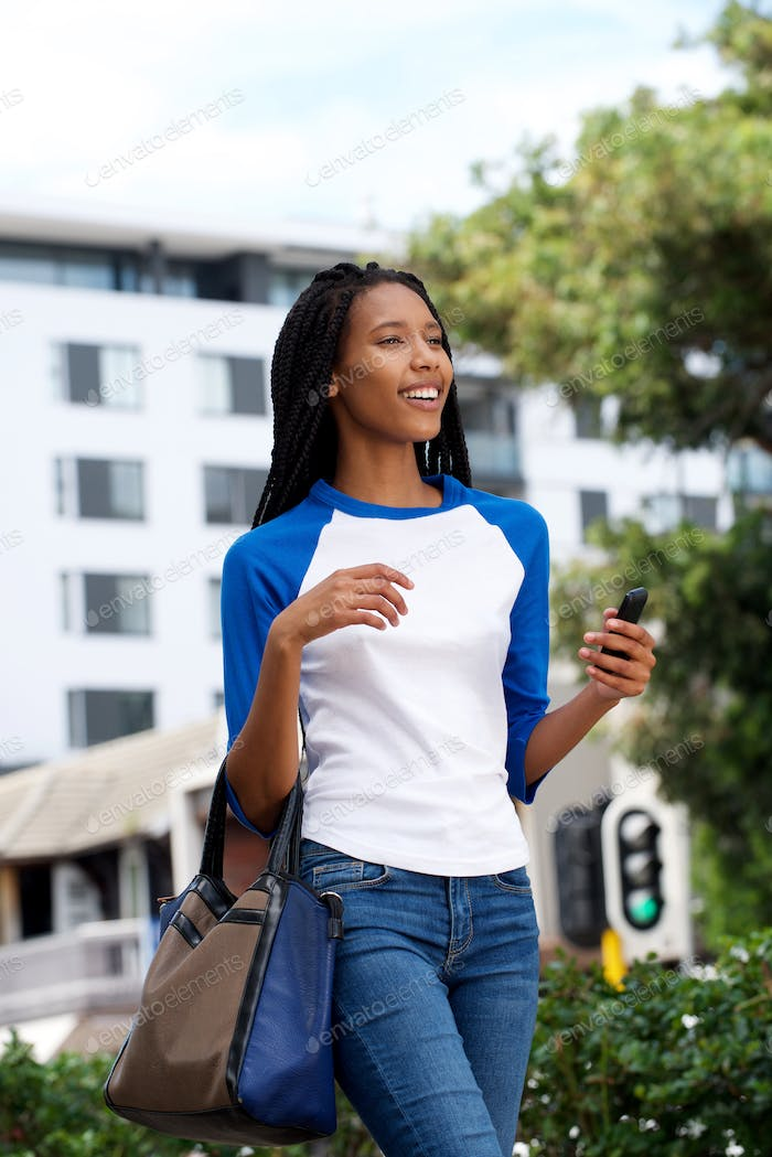 happy young african woman walking with bag and mobile phone