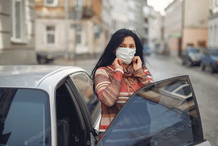 Woman in a mask stands on the street by the car