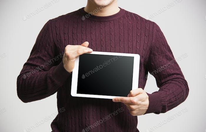 Junger Mann hält eine Tablette, zeigt seinen Bildschirm, Mittelteil