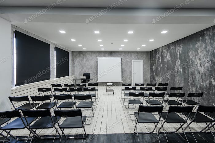 Room for lecture with a lot of dark chairs. Walls are white, loft interior. On the right there is a