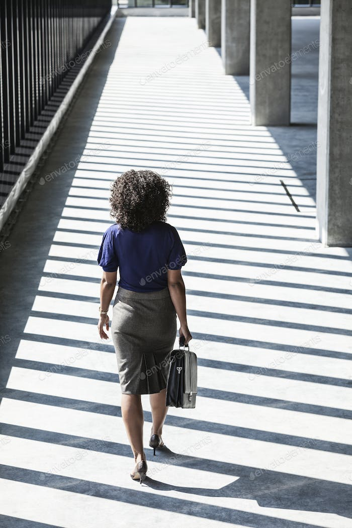 Businesswoman walking through large empty office space lit by the afternoon sun.