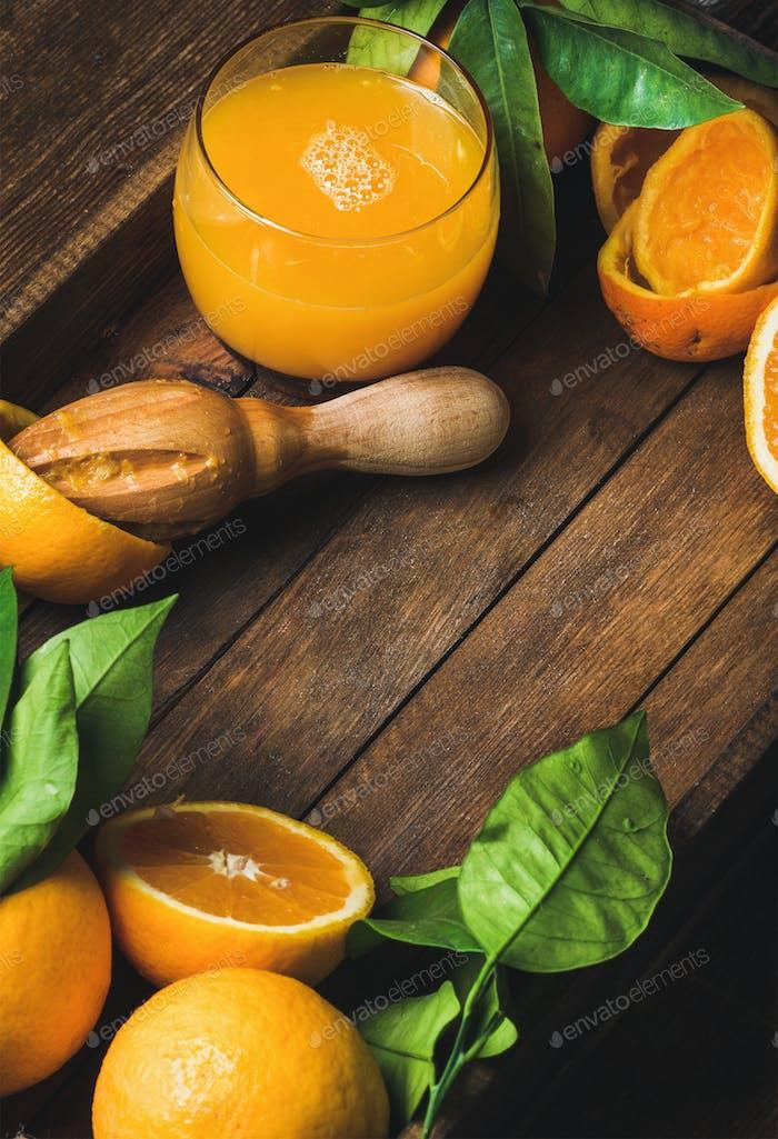 Glas frisch gepresster Saft und frische Orangen