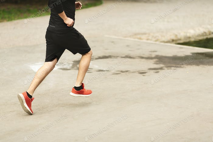 Unrecognizable male runner in red sneakers jogging outdoors