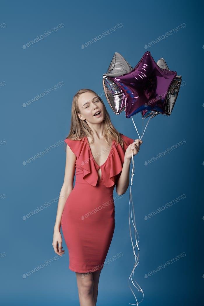 Frau in rotem Kleid hält Ballons.
