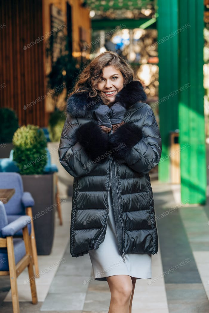 ?harming girl dressed in black down jacket with fur poses in the street