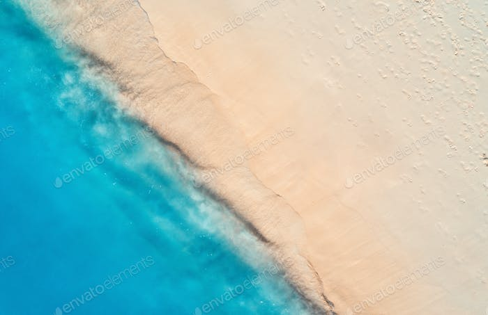 Aerial view of clear blue sea with waves and empty sandy beach