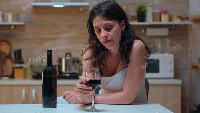 Woman looking at a glass of wine