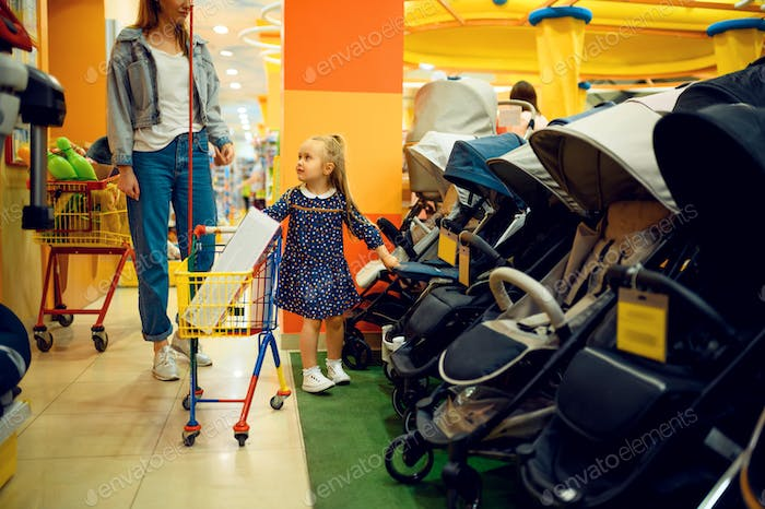 Mother and little girl buying baby stroller