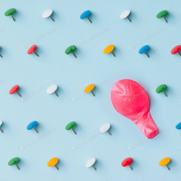 Pink baloon with colorful pins on blue background. Adversity or unique concept.