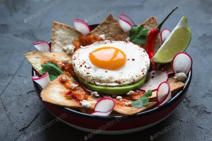 Mexikanisches Frühstück: Chilaquiles mit Ei, Avocado und Gemüse Nahaufnahme auf einem Teller