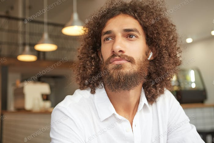 Close-up photo with beautiful bearded male in white shirt sitting in cafe, looking thoughtful aside