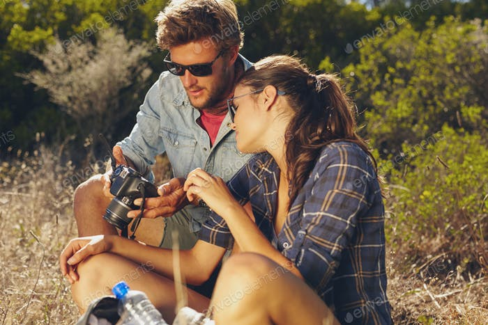 Young couple outdoors looking at pictures on digital camera