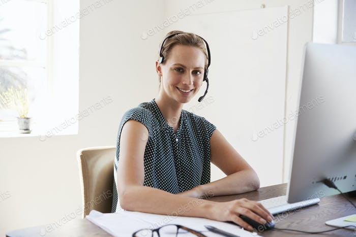 Young woman using headset and computer smiling to camera