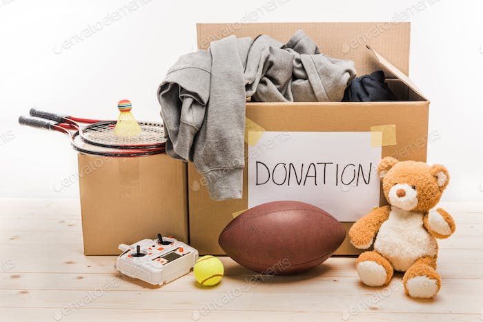 cardboard boxes with donation clothes and different objects isolated on white, donation concept