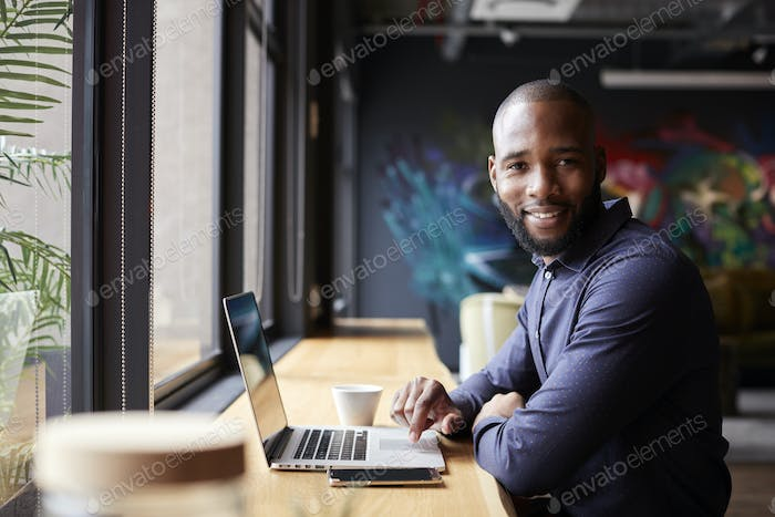 Mid adult black male creative sitting by window in cafe using laptop, turning and smiling to camera