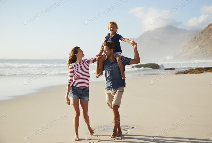 Parents Carrying Son On Shoulders On Beach Vacation