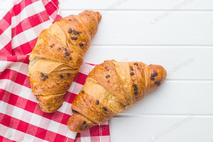 Zwei Croissants mit Schokoladenkrümeln.