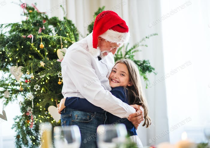 A small girl and senior grandfather with Santa hat hugging at Christmas time.