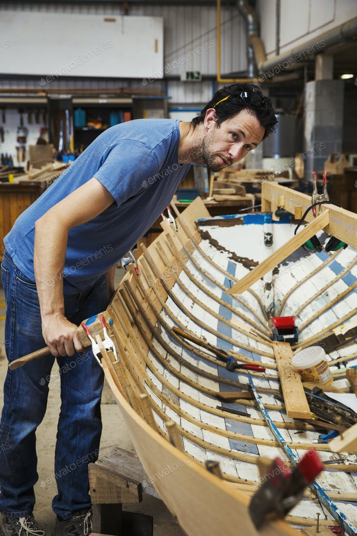 Man standing in a boat-builder's workshop, working on a wooden boat hull.