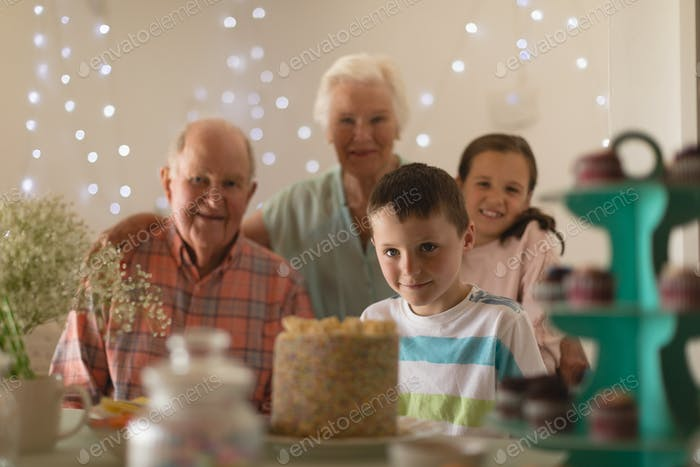 Multi-generation family celebrating birthday of grandson with a birthday cake at home