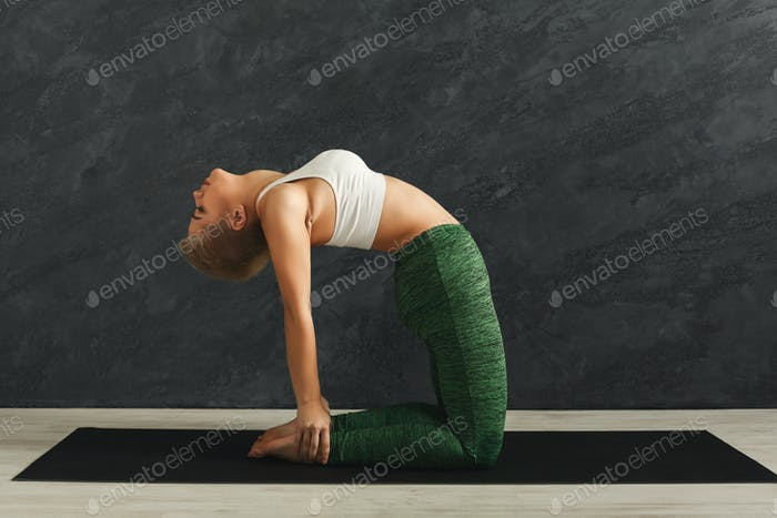 Woman training yoga in camel pose