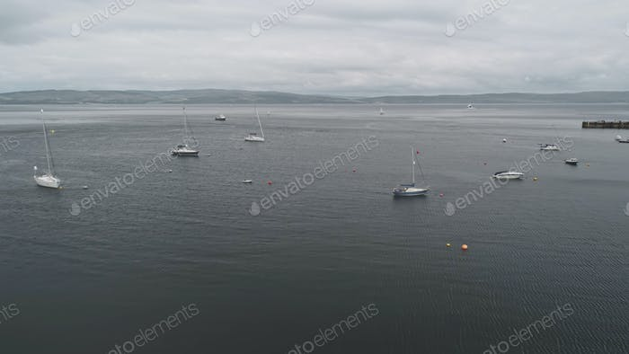 Yachts, ships at ocean bay aerial. Nobody nature seascape. Water transport at open sea. Arran Island