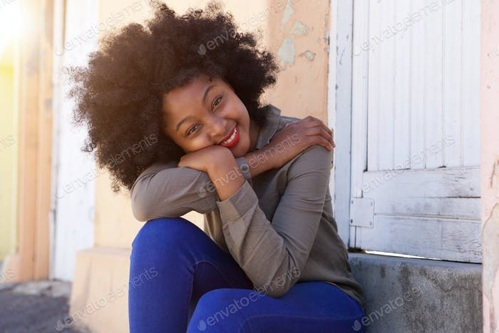 glückliche junge Frau sitzt auf Stufen lehnend Kopf auf den Armen