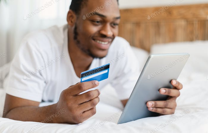 Guy Holding Tablet And Credit Card Shopping Online At Home