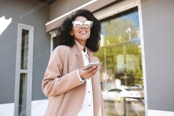 Pretty girl with dark curly hair strolling in coat and white shirt